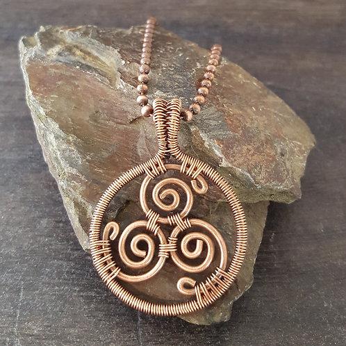 Copper wire woven triskele design pendant.