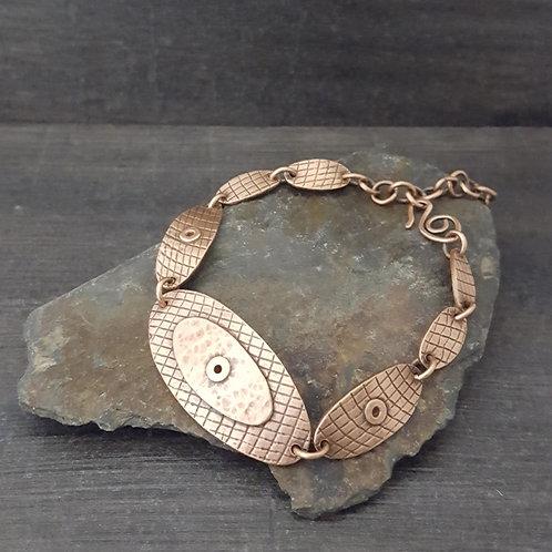 Oval textured copper link bracelet with rivet details.