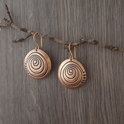 Oval domed copper earrings with spiral design.