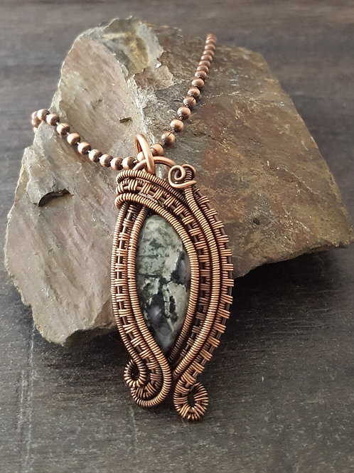 Copper wire woven pendant featuring a moss agate stone.