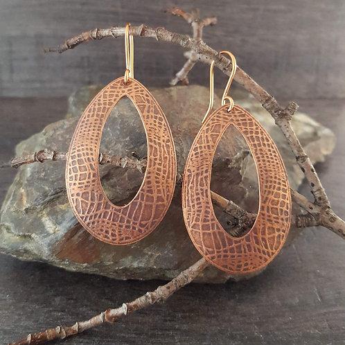 Open teardrop shaped texture patterned copper earrings.