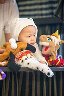 A baby gazes at a puppet