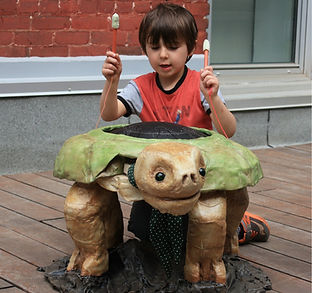 A boy plays a large turtle drum