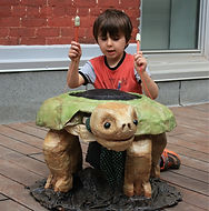 A boy drums a giant turtle pupet.