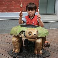 A boy drums a giant turtle pupet.