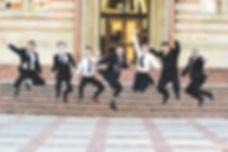 Men of YOUTHphonics strike a jumping posein front of Powell Library.