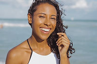 laughing-black-woman-in-swimsuit-on-beac