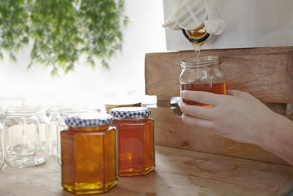 Honey being poured into a jar from a dispenser