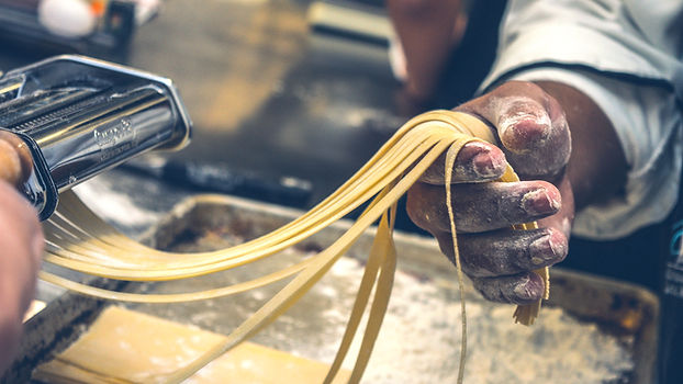An artisan works some pasta in a pasta factory. He has flour-stained hands