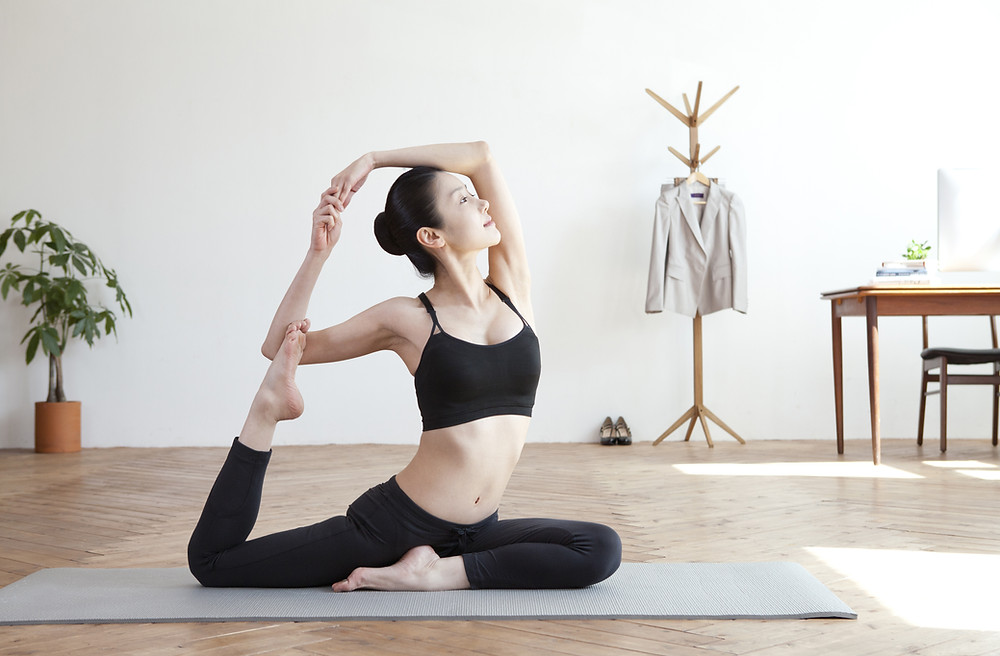 A young woman performs an advanced yoga pose