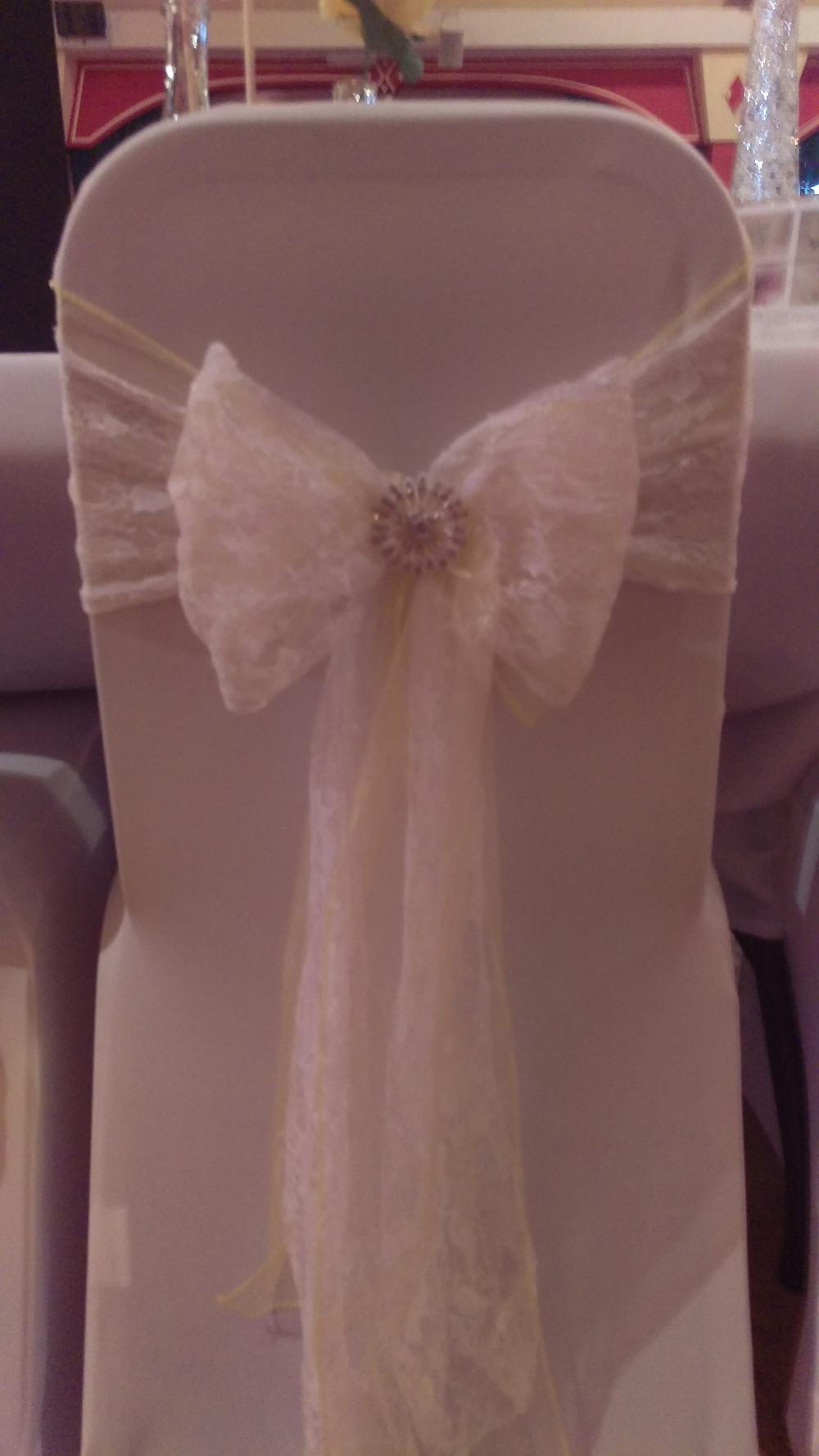White Lycra chair cover with Double Sash - Yellow Organza sash with lace sash tied over and cluster brooch. Wedding Venue Table Decoration by Embellish Venue Styling Kent - www.embellishvenuestyling.uk