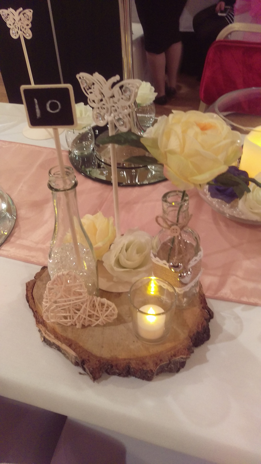 Rustic Wood Slice Centerpiece with Table Number, Rose, Wicker Love Heart, Glass Bottles Wedding Venue Table Decoration by Embellish Venue Styling Kent - www.embellishvenuestyling.uk