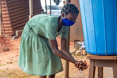 african school kid washing her hand from