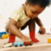 Jeune bébé jouant à quatre pattes avec un train en bois