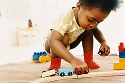 toddler playing with train set