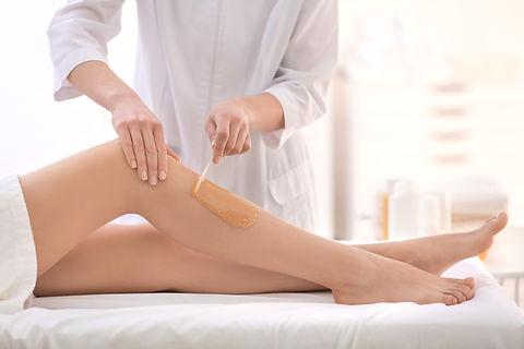 Beautician waxing female legs in spa cen