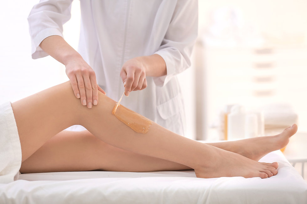 Beautician waxing female legs in spa cen