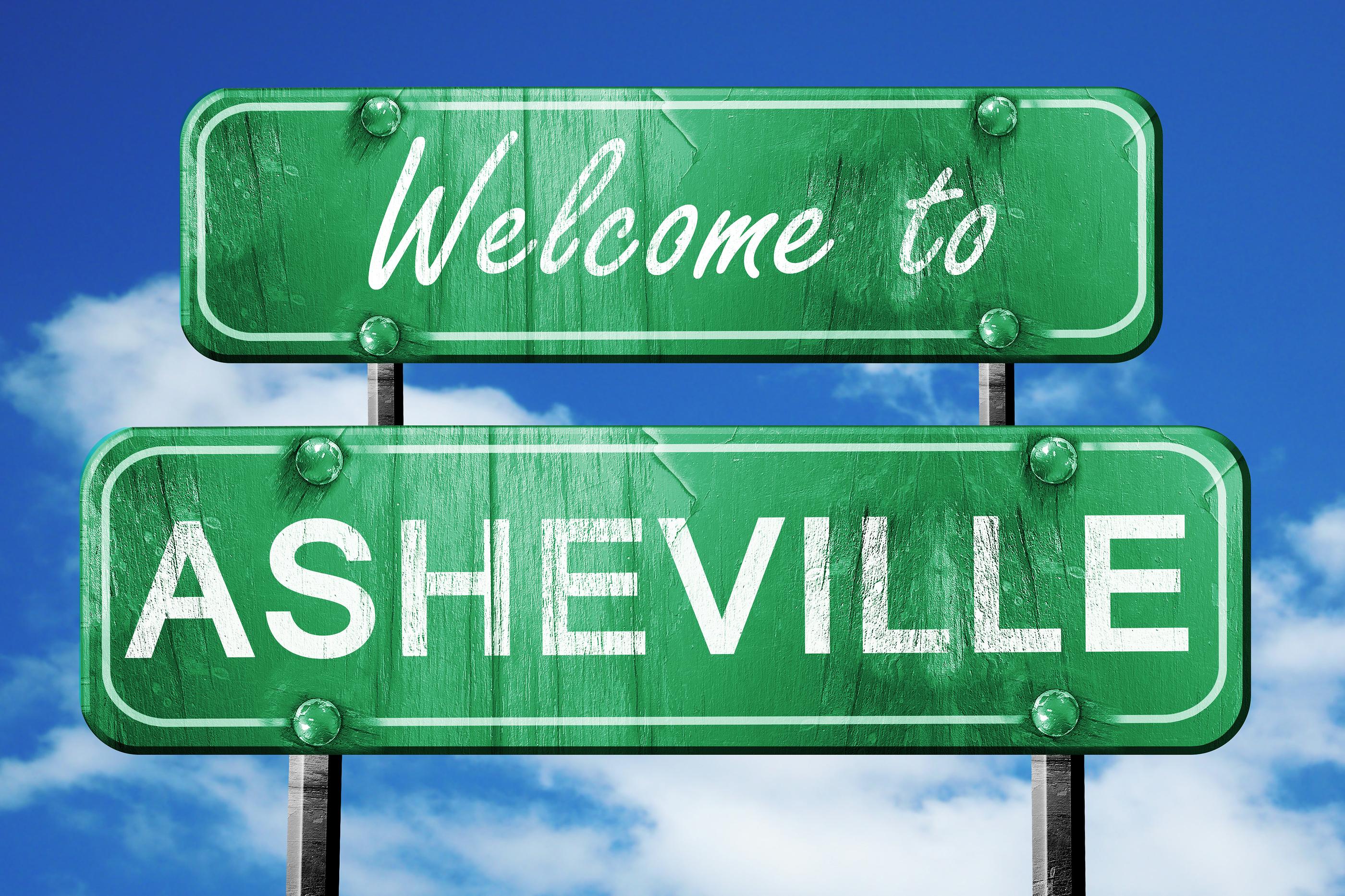 asheville vintage green road sign with blue sky background
