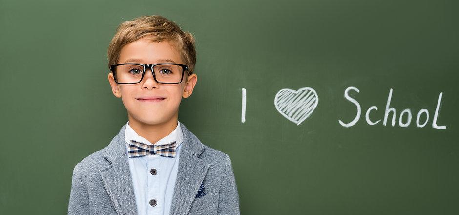 smiling schoolboy in eyeglasses next to