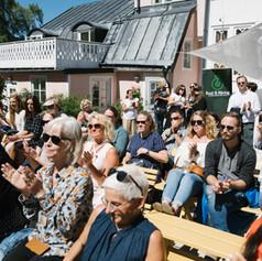 Sittande publik utan tak. Foto Linnea Ronström