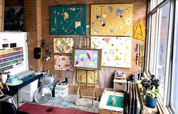 Artist Selva Veeriah's studio. A wide view of the room with abstract paintings, studio equipment, co