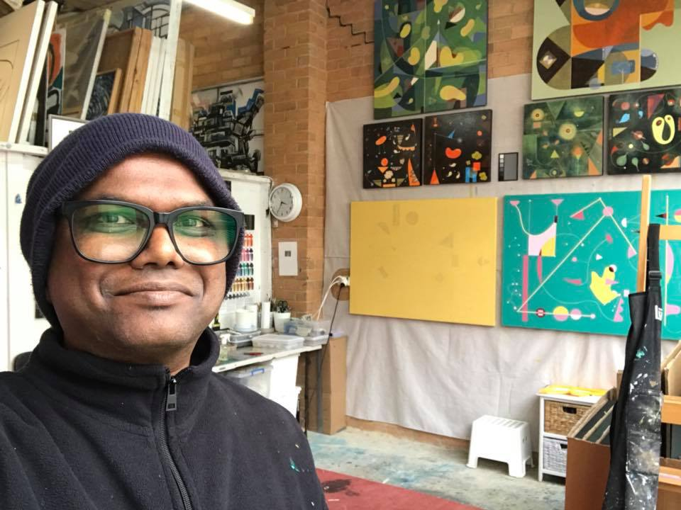 Artist Selva Veeriah in his studio. He is dressed in a beanie and fleece jacket. In the background a