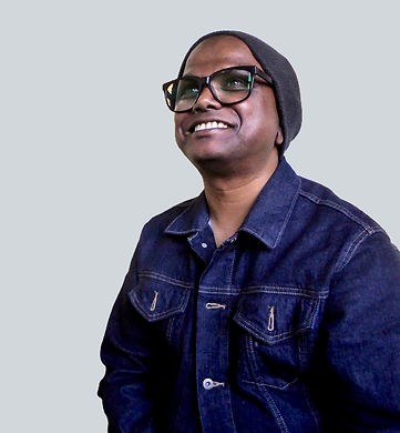 Artist Selva Veeriah's profile pic. He is wearing a grey beanie, dark denim jacket, big trendy glasses, and sporting a lovely smile.