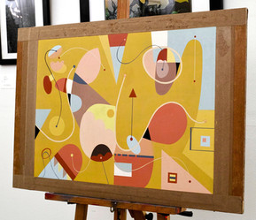 Acrylic painting S256 mounted on an easel in the studio gallery. Geometric/organic shapes and lines. Dominant colours are yellow ochre, red, and light blue.