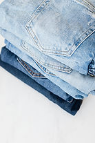 Canva - Stack of jeans on white marble s