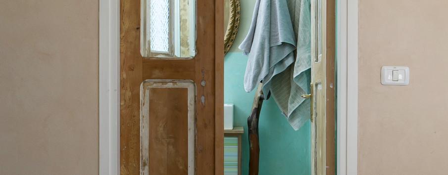 חדר אמבטיה- דלת עץ עתיקה, מתלה עץ למגבות