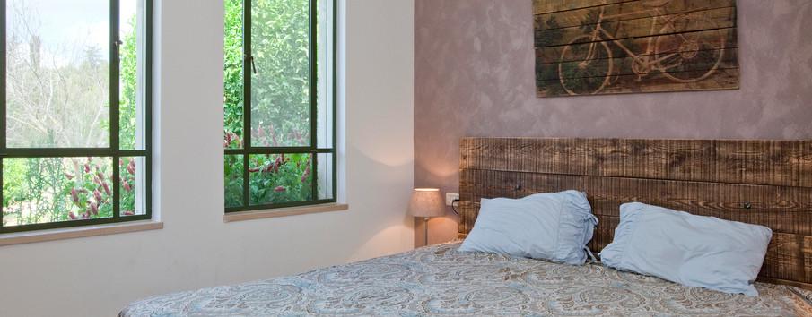 מיטה שנבנתה לה מקורות עץ ישנים ותמונה על קיר המיטה שהיא למעשה הדפסה של יצירה שלי על משטח עץ.