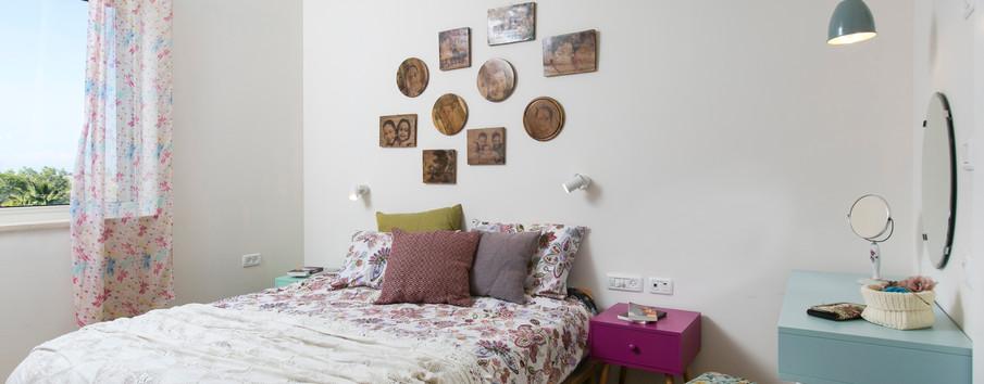 """חדר שינה- תמונות המשפחה עוצבו על """"פלטות עץ"""" ונתלו כתמונות."""
