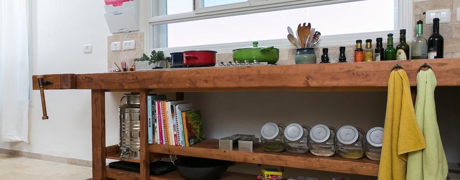 שולחן נגרים שהותאם בצרכיו ובמידותיו מראש כחלק בלתי נפרד מתכנון המטבח; יחידת הגז, מקום לשמן הזית ושאר צרכים