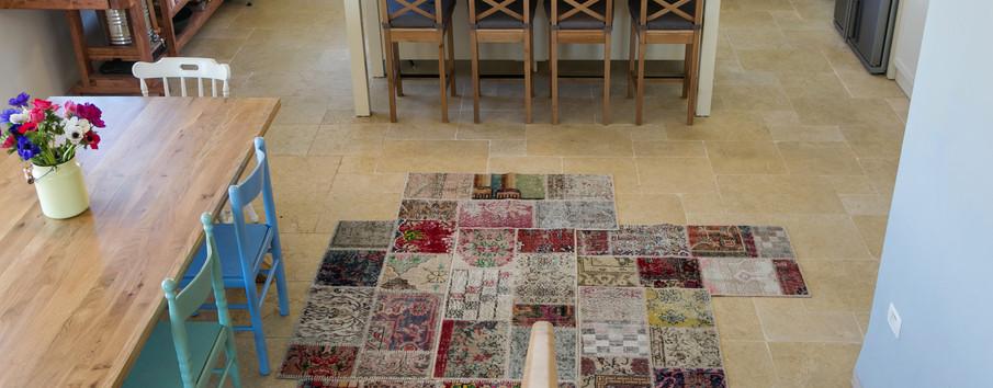 מקבץ שטיחים אקלקטי במעבר לכיוון המטבח