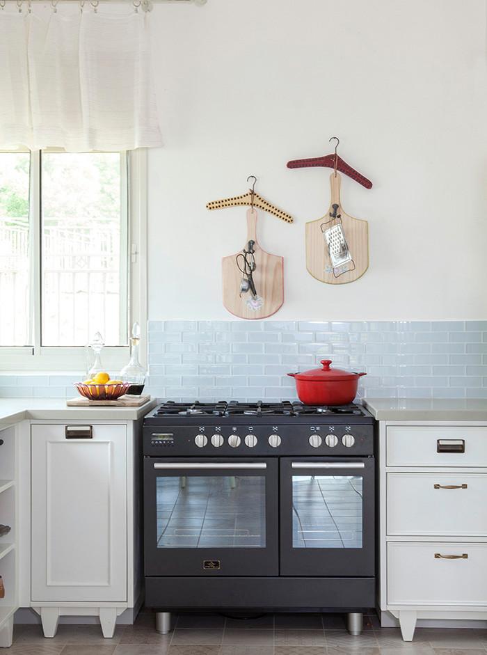 """אריחי זכוכית מלווים את חזית המטבח. """"יצירות"""" של הלקוחות מעטרות את הקירות"""