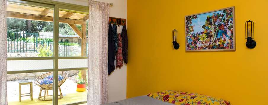 חדר השינה נבחר צבע כתום האהוב על בני הזוג- ברקע מרפסת עם ריצוף בטון בצבע צהוב