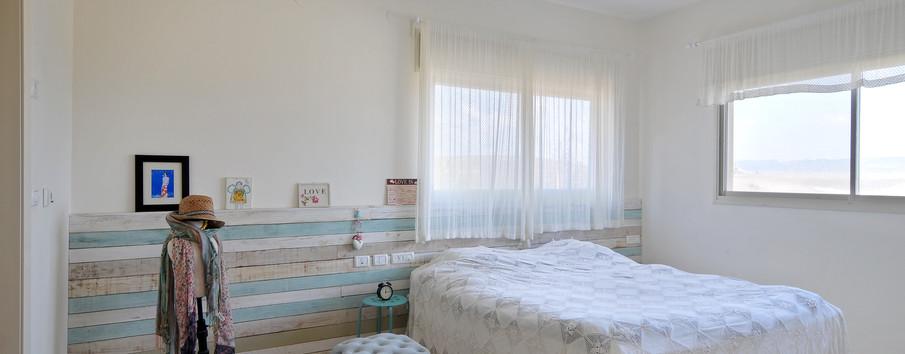 קיר עץ ממוחזר מעטר את גב המיטה וגם מהווה מדף לתמונות