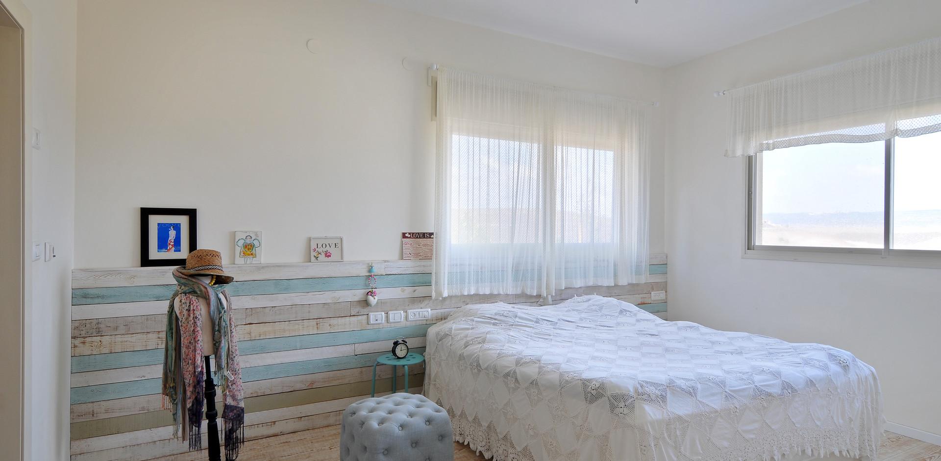 חדר שינה הורים- קורות העץ מעטרות את קיר המיטה