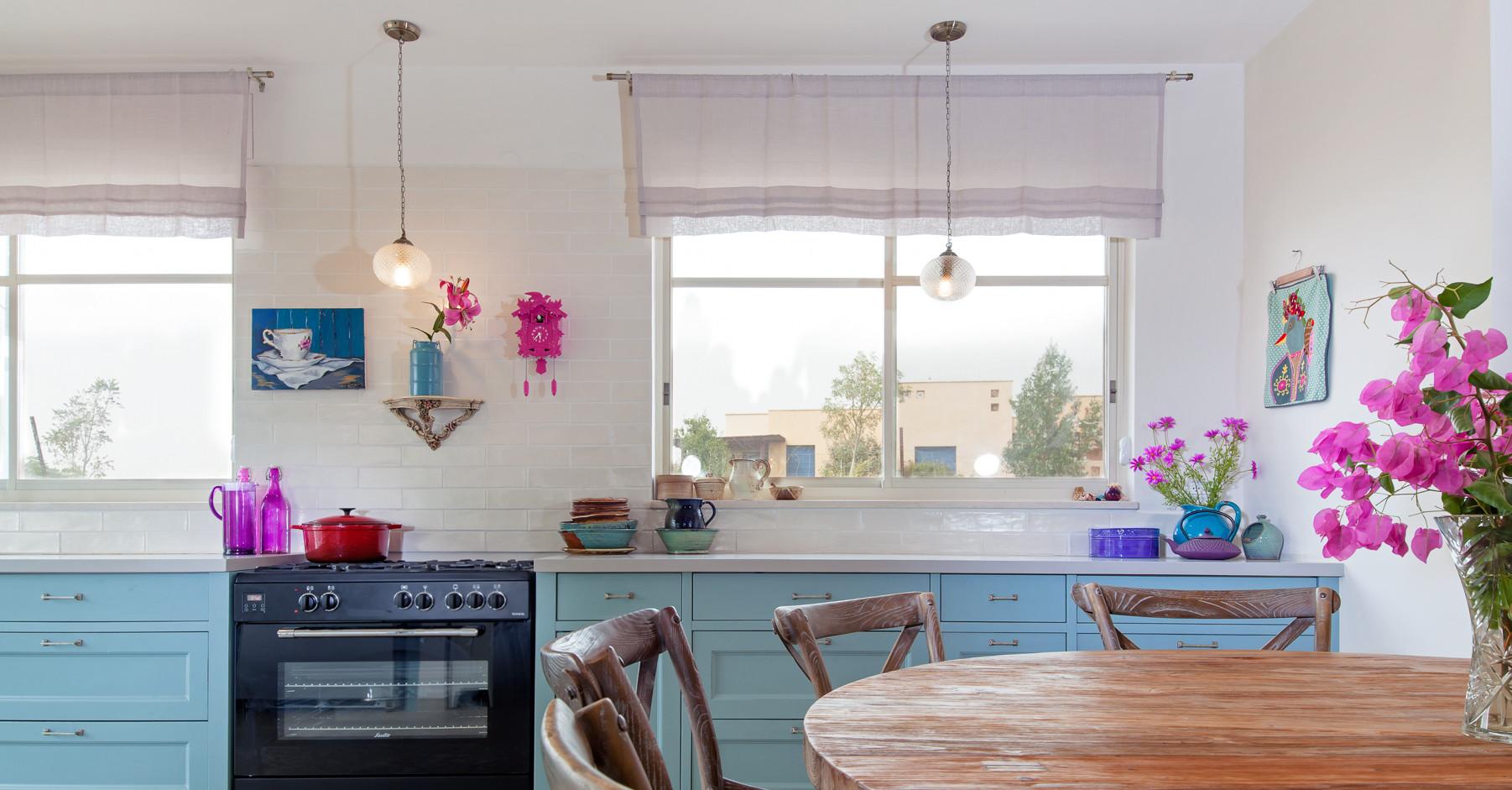 מטבח תכול עם נגיעות צבע סגול- ורוד. הרבה שמחה . פריטי עיצוב של בני המשפחה מקשטים את המטבח
