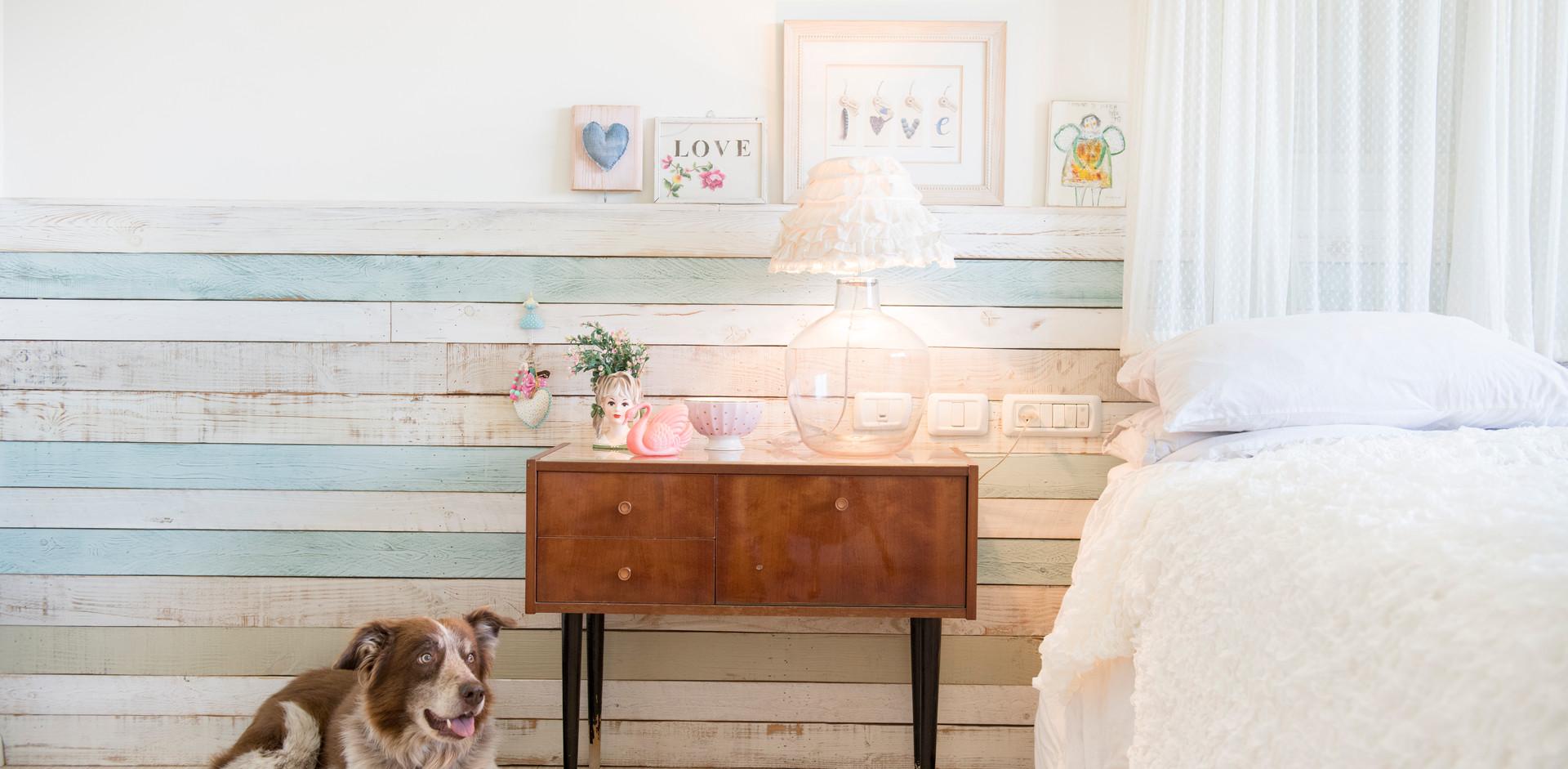 קיר עץ ממוחזר מעטר את גב המיטה וג מהווה מדף לתמונות