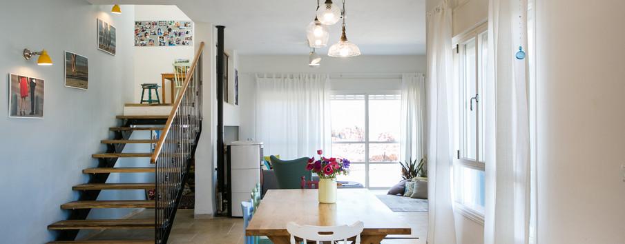 חלל מרכזי מכיוון המטבח. תאורה ייחודית שעוצבה במיוחד לטעם הלקוחות, מקבץ כסאות אקלקטי מדברים בהרמוניה עם הסלון וגרם המדרגות