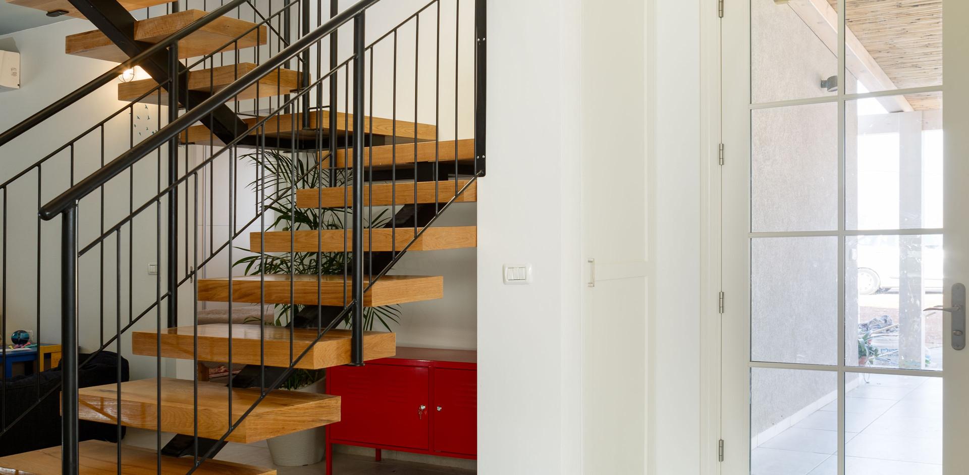 גרם מדרגות מהווה  אלמנט עיצובי מרכזי וחוצץ בין החלל הציבורי לפרטי. יצירה מברזל מעטרת את חלל המדרגות