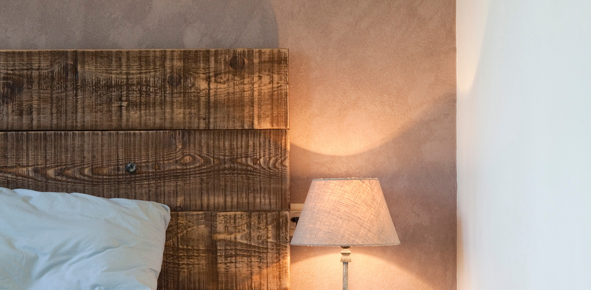 שידה ליד המיטה היא יצירה של שילוב  מגרות פח שלוקטו בשווקים עם יחידת עץ מעובדת