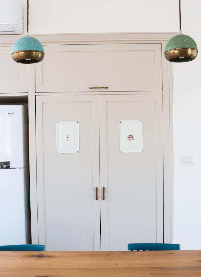 מכסי סירים שאהבנו שובצו כיצירות בתוך דלתות ארון המטבח