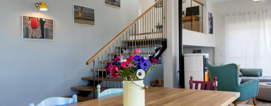 מדרגות מיוחדות, צבע, פריטי יצירה של בני המשפחה ומעקה ייחודי מעטרים את החלל כולו.