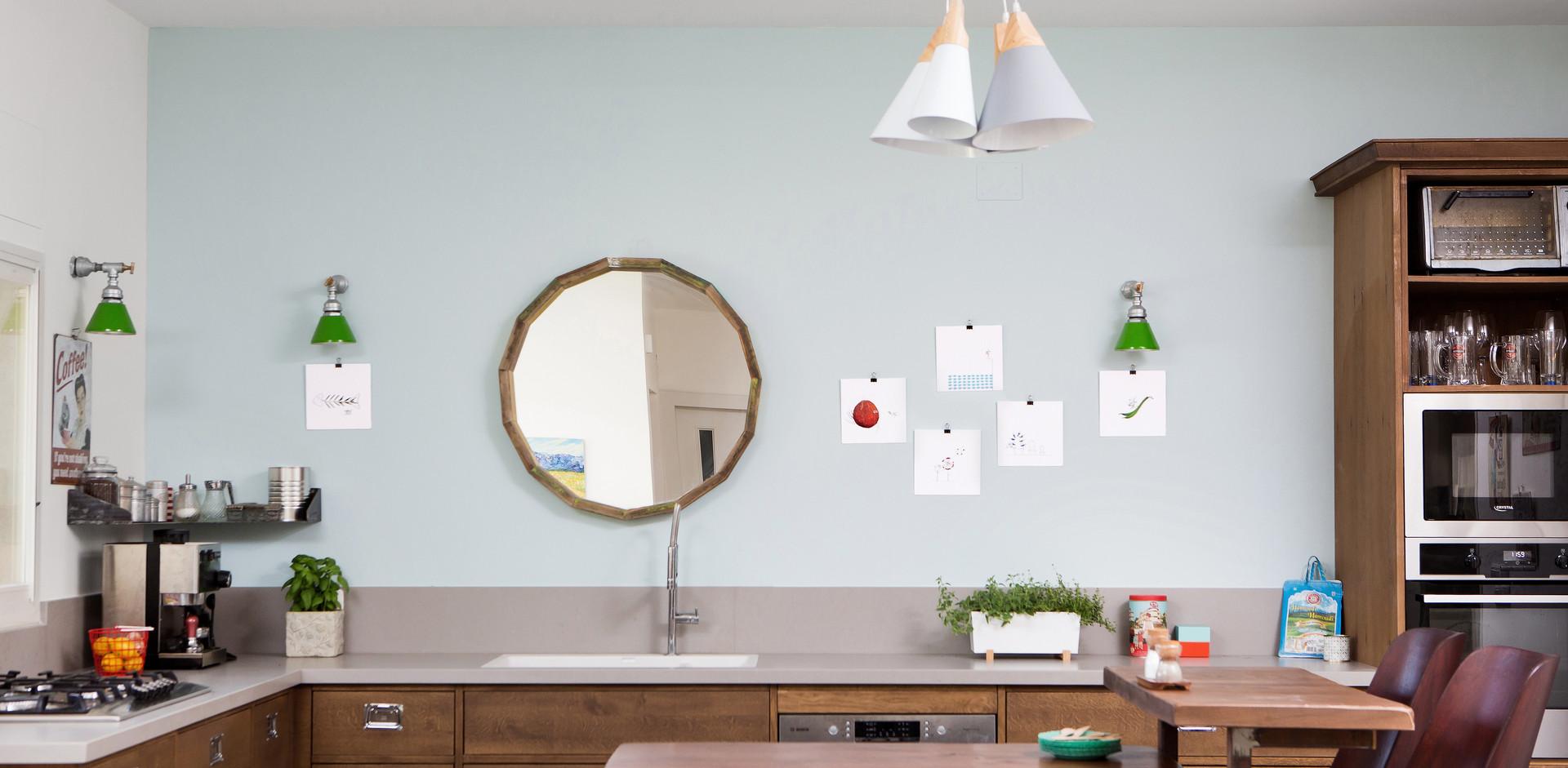 קיר ללא חלון זוכה לתשומת לב ייחודית עם מראה מעוגלת המכניסה את חלל הבית לעומד בגבו לחלל המרכזי