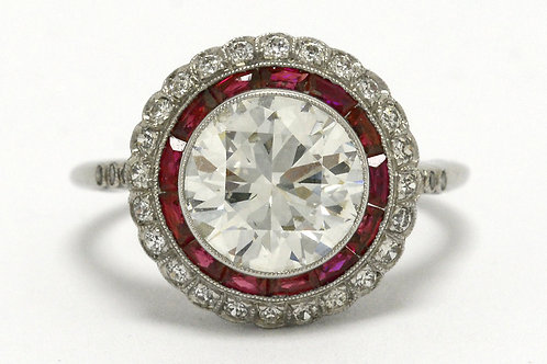 A diamond engagement ring with a ruby gem halo, a platinum Edwardian style design
