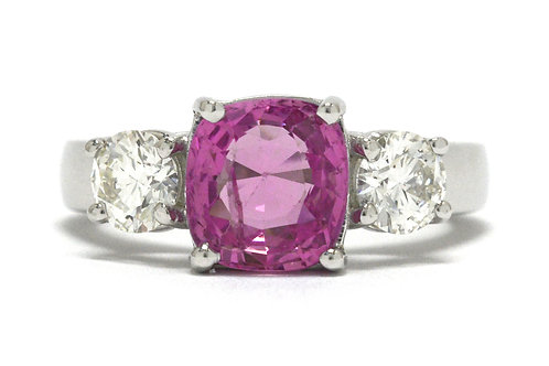 An 18K white gold 1 pink sapphire 2 diamond engagement ring