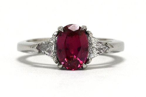 An oval pink sapphire engagement ring accented by 2 triangle diamonds platinum trinity design