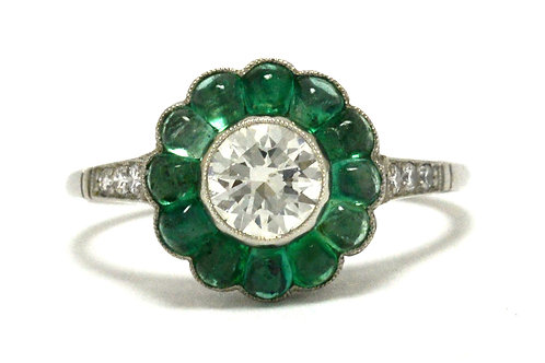 A diamond platinum engagement ring with emerald flower petals